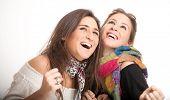 Jóvenes hermanas una rubia, la otra morena riendo juntos