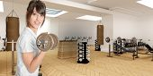 Young woman in a gym lifting a dumbbell
