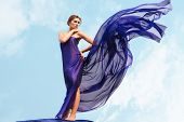 Charming woman folded in dark blue chiffon shawl with cloudy sky at background