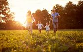 Young cheerful family together enjoying outside poster
