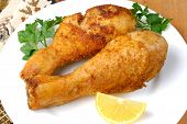 stock photo of fried chicken  - Fried chicken legs with lemon on the white plate - JPG