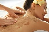 Young woman receiving scrub massage in spa salon poster