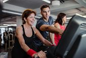 Two Cheerful Female Seniors In Gym With A Young Trainer Doing Cardio Work Out. poster