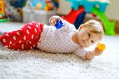 Little Cute Baby Girl Learning To Crawl. Healthy Child Crawling In Kids Room With Colorful Toys. Bac poster