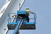 stock photo of cherry-picker  - Blue metal cherry picker with workers partially in view working on a small section of a bridge girder set against a blue sky - JPG