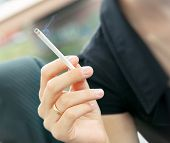 Cigarette Smoking In Women's Hand. Soft Focus.