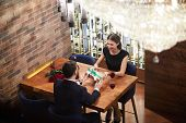 Happy young woman taking giftbox passed by her boyfriend by table during romantic date in classy res poster