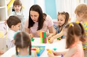Kids Playing With Educational Toys At Table In Kindergarten. Nursery Teacher Looking After Children poster