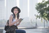 Beautiful Asian Solo Tourist Woman  Reading The Travel Guide Book Searching For For Tourists Sightse poster