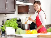 stock photo of apron  - Cooking woman in kitchen stirring in pot making food for dinner - JPG
