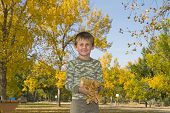 Happy Boy plays with fall leaves