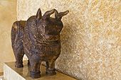 picture of plinth  - Indigenous crafted from dark Indian wood probably mango tree  ornate bull freestanding on a plinth against bare mineral tiled wall - JPG