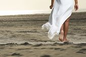 stock photo of barefoot  - An African American girl is walking on the beach - JPG