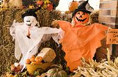 stock photo of jack-o-laterns-jack-o-latern  - A fall display of ghosts pumpkins hay and fall leaves - JPG