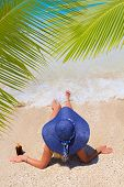image of suntanning  - Beautiful young woman with straw hat suntanning on the beach - JPG