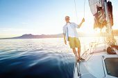 stock photo of life-boat  - sunrise sailing man on boat in ocean with flare and sunlight on calm morning on the water - JPG