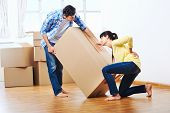 stock photo of injury  - back injury from carrying heavy box while moving home - JPG