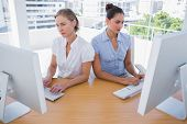 Businesswomen working side by side at desk in office