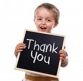 Child holding a thank you sign standing against white background