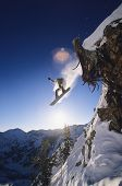picture of snowboarding  - Low angle view of snowboarder jumping from mountain ledge - JPG