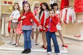 MOSCOW - MAR 18: Anya 7 years old and Jeanette 6 years old trying on red clothes together with manne