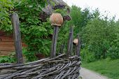 Traditional lath fence around a farmer's house with clay pots on top of stakes in open air museum Ki