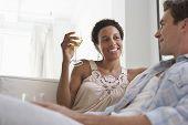 Pareja joven multiétnica con vino copas en sala de estar en casa