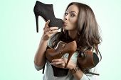 stock photo of shoe  - funny portrait of pretty brunette girl with many heels in her hands in the sales season - JPG