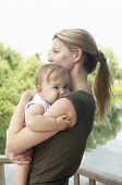 Seitenansicht einer jungen Mutter, die Tochter gegen den See
