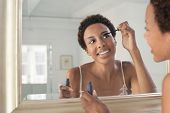 Closeup of an African American woman applying mascara in mirror at home