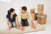 Happy young couple unrolling carpet in new home