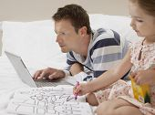 Father using laptop by daughter as she draws in bed