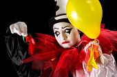 Sad Pierrot clown holding the left-overs of his balloons