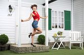 stock photo of girl next door  - Smiling woman in shorts poses next to simple entrance door of country house - JPG