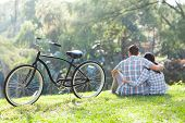 back view of romantic teenage couple sitting outdoors with bicycle next to them