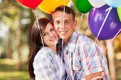 casal teen romântico ao ar livre com balões de hélio a sorrir
