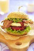 Egg burger with tomato, salad, onuion and fried bacon