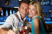 Couple Enjoying Cocktail In Bar