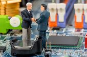 two managers talk on the motherboard of a computer standing