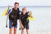 Father And Son With Scuba Diving Equipment On Beach Holiday