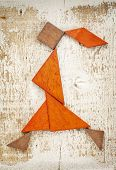 abstract figure of a walking or running girl built from seven tangram wooden pieces, a traditional C