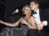 Happy young glamorous couple with champagne flutes in limousine