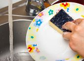 Woman Using A Yellow Sponge To Clean The Plate