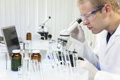 A male medical or scientific researcher or doctor using a microscope in a laboratory with test tubes