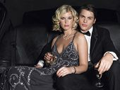 Portrait of young glamorous couple with champagne flutes in limousine