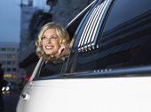 Sonriente a joven celebridad femenina en limusina, mirando por la ventana