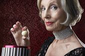 foto of chokers  - Closeup portrait of a wealthy senior woman with box of candy - JPG