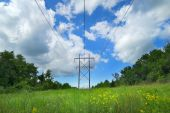picture of transmission lines  - Utility wires over a country meadow against a partly cloudy sky - JPG