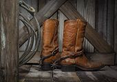 stock photo of black heel  - a pair of cowboy boots on a country porch - JPG