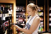 stock photo of liquor bottle  - Woman shopping for wine or other alcohol in a bottle store standing in front of shelves full of bottles and holding bottle in her hand and reading inscription - JPG